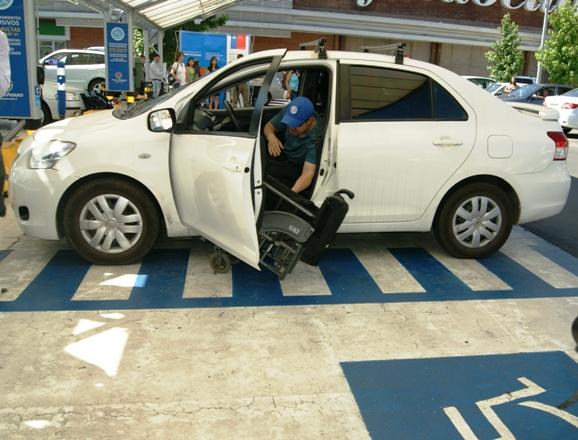 Persona con discapacidad física sube a su vehículo.