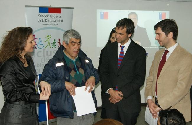 Autoridades entregándole el folleto en Braille a Jorge Villagra.
