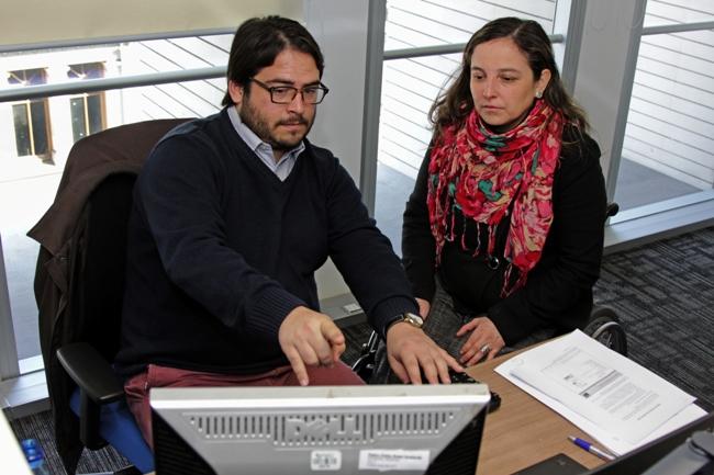 Mujer en silla de ruedas está sentada a un costado de un hombre que apunta a un monitor de computador, en clara posición de trabajo.